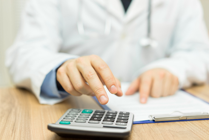 doctor is calculating cost of treatment